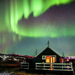 Northern Lights visible above small cabin in Iceland iStock_000066132119_Large 250 250