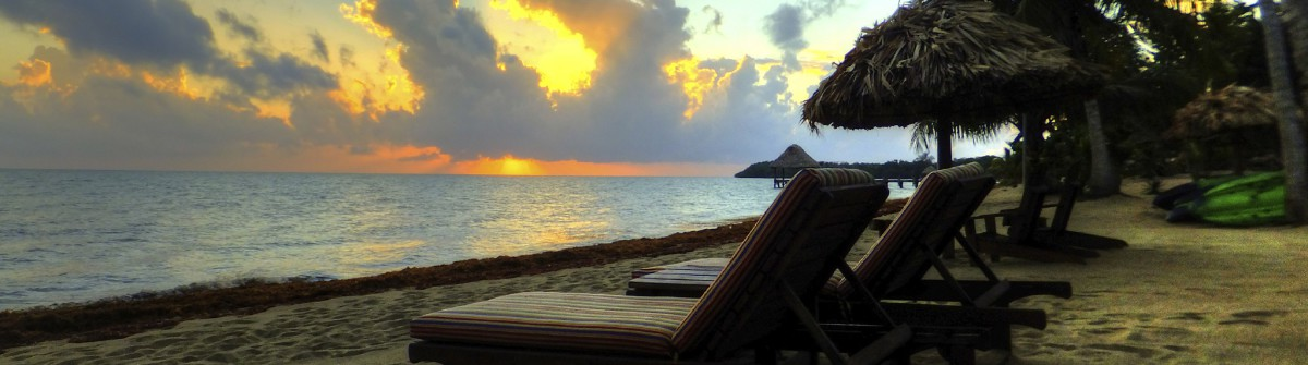 Belize sunset with beach lounge chairs