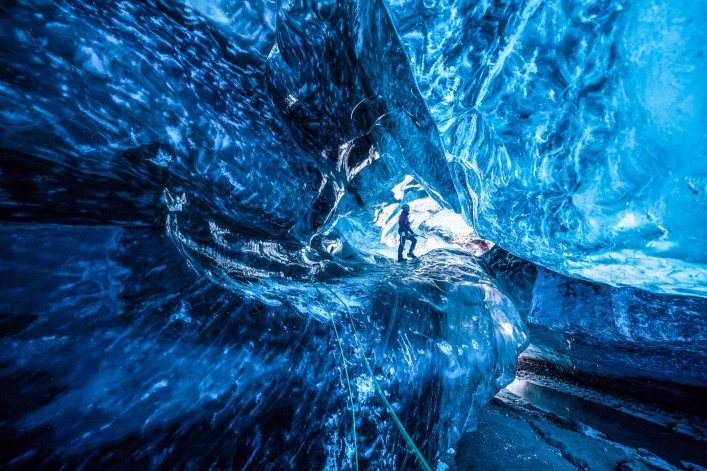 Inside an icecave in Vatnajokull, Iceland. A climber silhoutted against the ice. The ice is thousands of years old and so packed it is harder than steel and crystal clear. These caves are formed by meltwater that rushes from over and underneath the glacier and creates these wonderful sights
