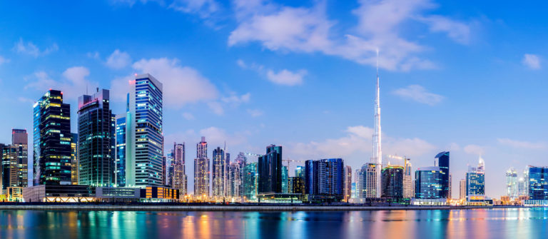 Illuminated Dubai city skyline at sunset, United Arab Emirates.