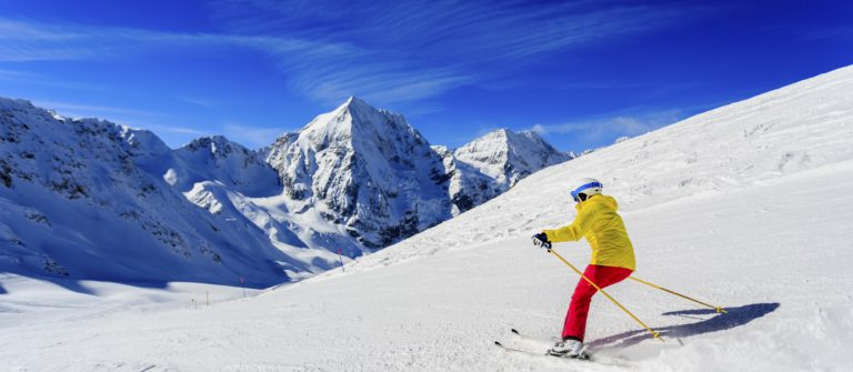 Ski, skier on ski run – woman skiing downhill, winter sport