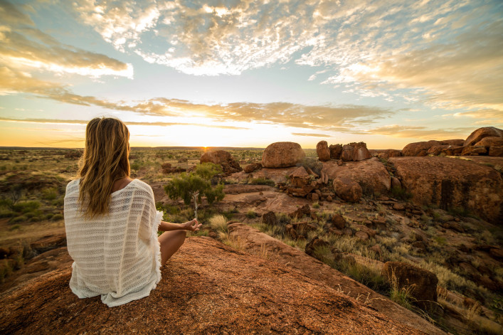 Young woman at the devil's Marbles sitting on a boulder exercises yoga at sunrise. Devils Marbles Conservation Reserve, Northern Territory, Australia.