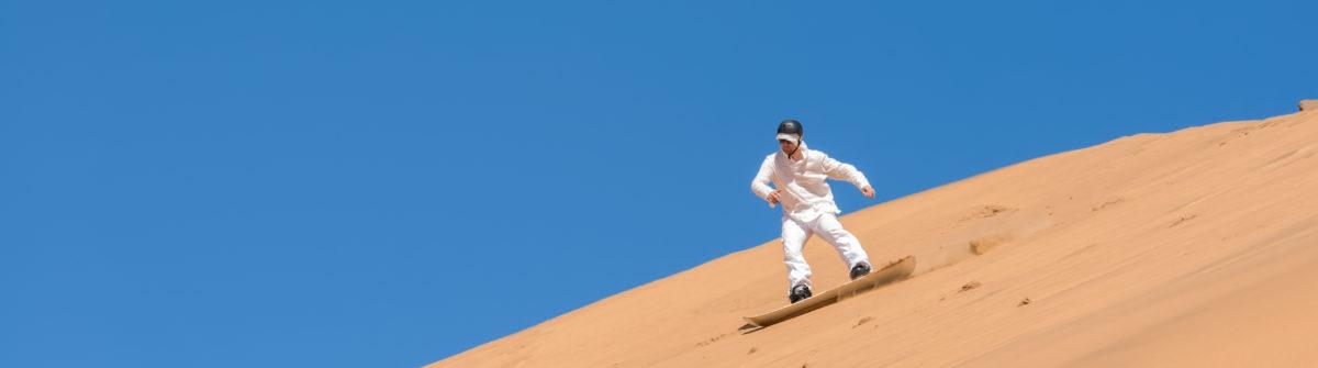 man-sandboarding-in-namibia-africa-shutterstock_195630167-1200×335