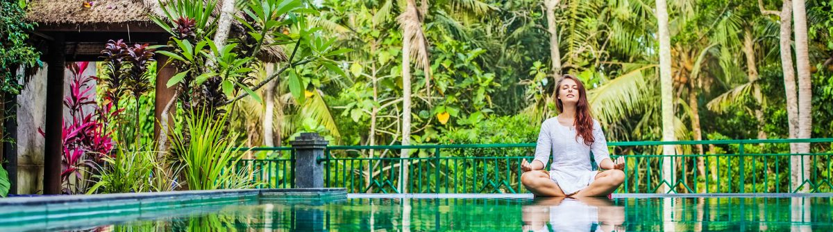 Woman meditation at gorgeous pool side of luxury tropical villa shutterstock_250381006-2