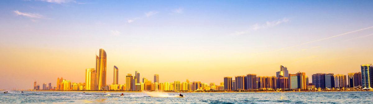 Beach with backdrop of Abu Dhabi skyline at sunset VAE iStock_000022783355_Large-2
