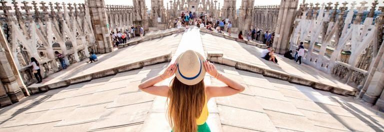 Back view on the female traveler standing on the rooftop of Duomo cathedral in Milan. Having great vacations in Milan_481189675