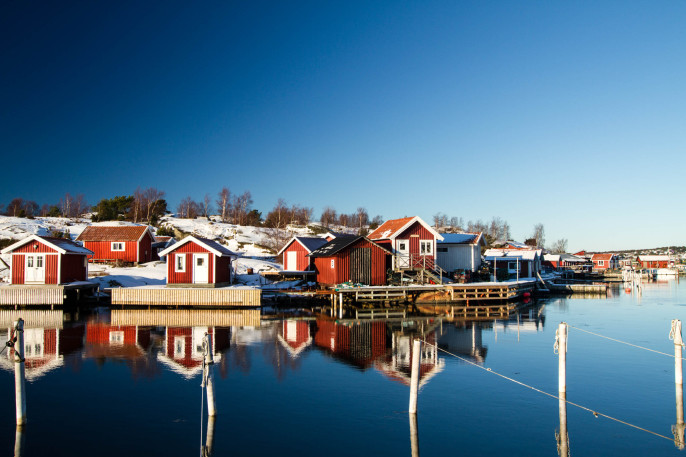 Red houses reflecting in water on Gothenburg archipelago iStock_000015101761_Large-2