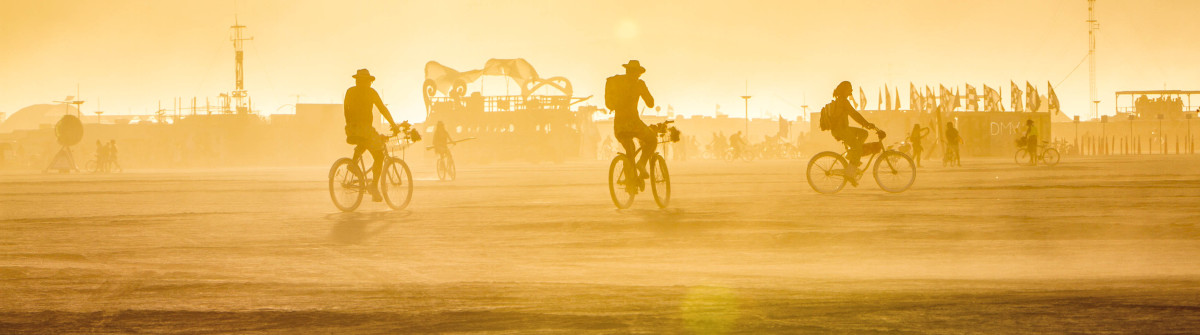 Friends riding with bikes in Burning Man festival on a warm sunny day shutterstock_374015302-2