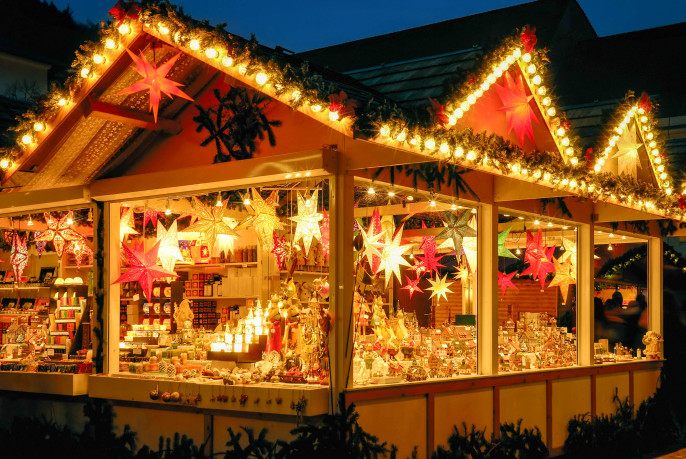 Illuminated Christmas fair kiosk with loads of shining decoration merchandise shutterstock_157503014-2